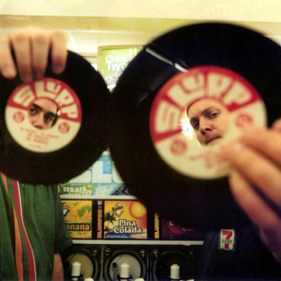 "Cut Chemist and DJ Shadow pose with 45 inch records in a 7 Eleven for the cover of ""Brainfreeze""."