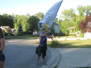 Mat Pflanz waves a homemade Amelia flag before a football game